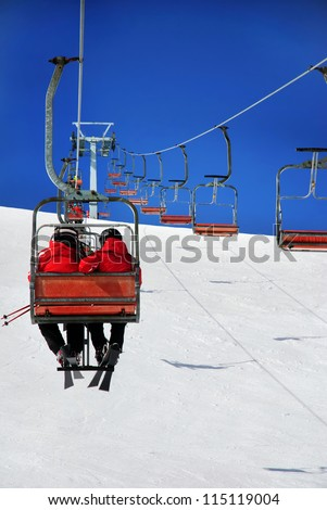 Skiers on a ski lift - stock photo