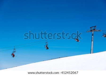 skiers on a skiing lift in the alps