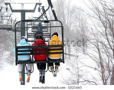 Skiers on chairlift at ski resort - stock photo