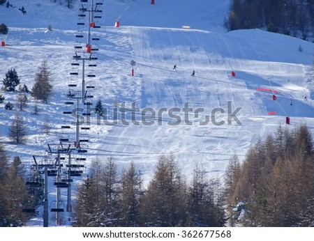 Skiers on ski runs in the French Alps in wintertime - stock photo
