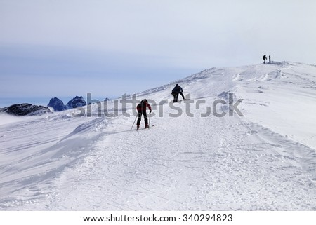 Skiers on ski slope at wind day. Caucasus Mountains, Georgia, ski resort Gudauri.