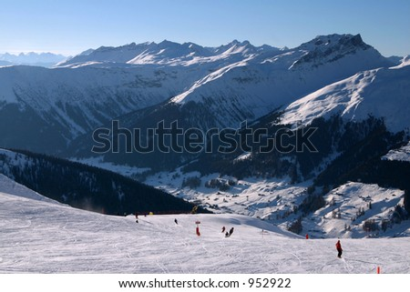 Skiers on their way down into the valley. Taken in Davos, Switzerland. - stock photo