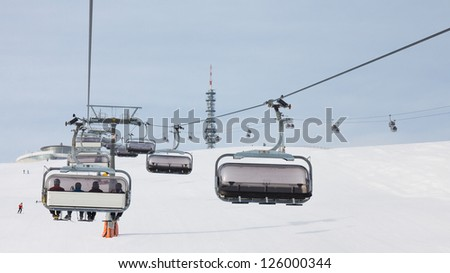 Skiers ride a chairlift in South Tyrol, Italy
