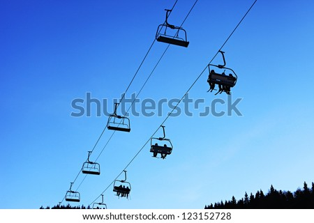 Skiers silhouettes on lift over blue sky. - stock photo