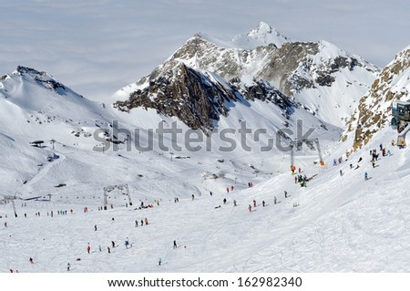 Skiers skiing on ski slope in a ski resort. Kitzsteinhorn, Austria - stock photo