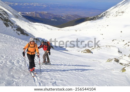 Skiers skinning uphill on steep mountain slope - stock photo