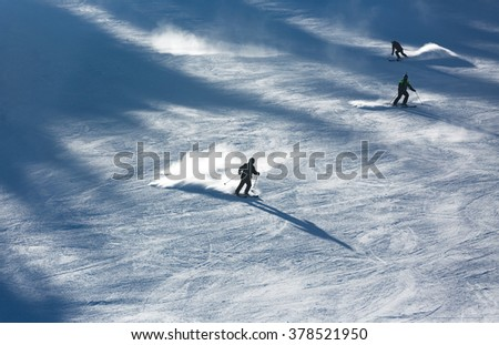 Skiers sliding from mountains - stock photo