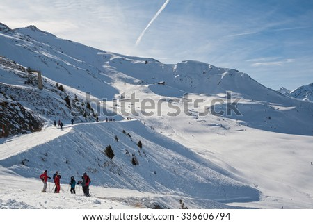 Skiers stand at edge of ski slopes, the Alps, Switzerland - stock photo