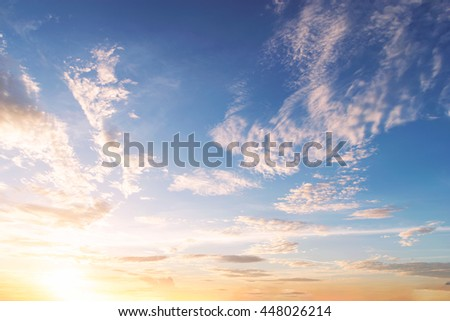 Skies are changing from blue to orange in the sunset. - stock photo
