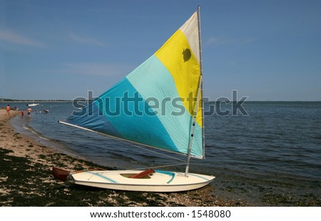skiff with sail up sitting on beach