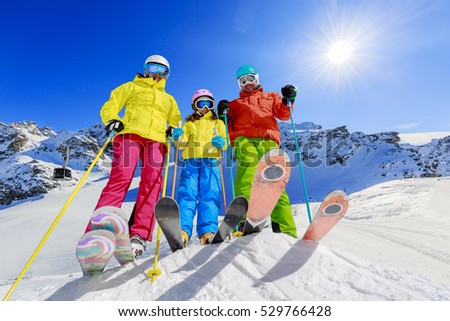 Skiing family enjoying winter vacation on snow in sunny cold day in mountains and fun. Cable car ski lift in background. Switzerland, Alps.