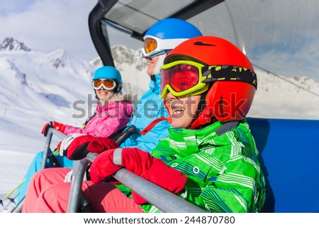 Skiing - happy skiers on ski lift - stock photo