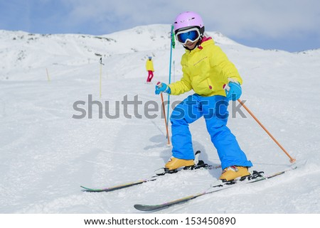 Skiing, skiers on ski run - child skiing downhill - stock photo