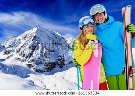 Skiing, snowboarding - portrait of young couple on winter holiday - stock photo