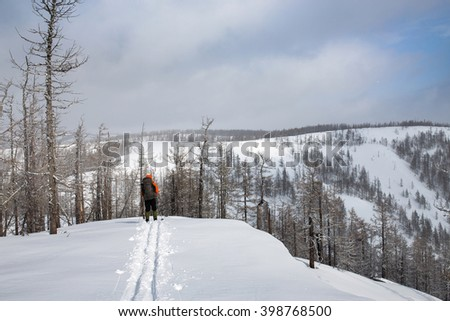 skiing trails man with backpack on snowy mountains Ridge