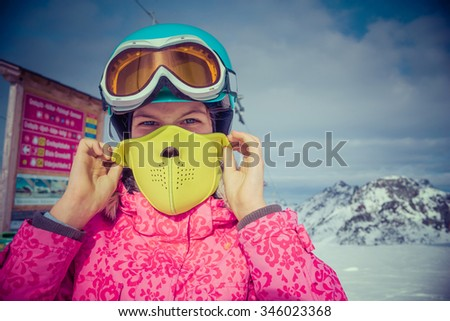 Skiing, winter, child - Portrait of young skier girl wearing mask in winter resort - stock photo