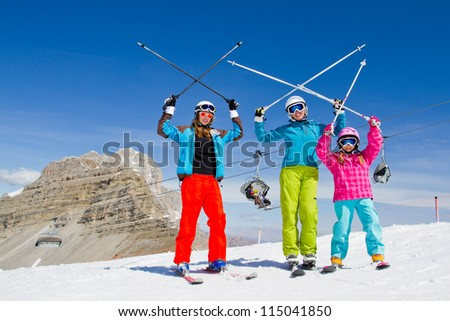 Skiing, winter fun - skiers on mountainside - stock photo