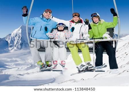 Skiing, winter - happy family ski team on ski lift - stock photo