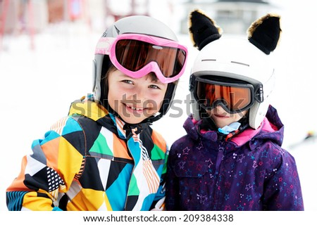 Skiing, winter sports - two adorable kid girls in helmets - stock photo
