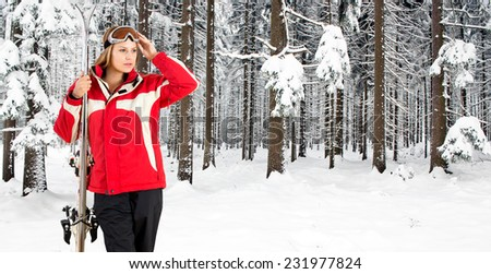 Skiing woman posing in the deep snow woth a forest, covered in fresh, powder snow, in the background - stock photo