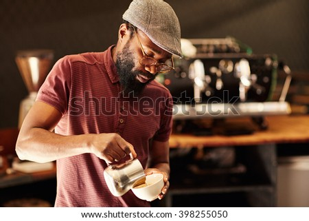 Skilled African barista pouring frothed milk into a cappucino - stock photo