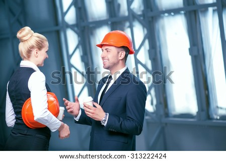 Skilled architects are standing and resting on a break. They are drinking coffee and discussing a new project. The workers are looking at each other and smiling. Copy space in right side - stock photo