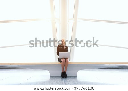 Skilled businesswoman with net-book on knee is phoning via mobile phone, while is sitting in co-working space. Modern female is using laptop computer and cell telephone to preparing for conference - stock photo