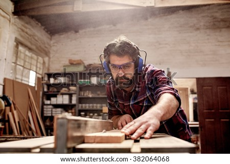 Skilled carpenter and small buiness owner working in his woodwork workshop, using a circular saw to cut through a wooden plank - stock photo