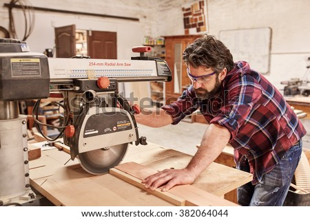 Skilled carpenter in his woodwork workshop, cutting a piece of wood with a radial arm circular saw, and wearing safety goggles - stock photo