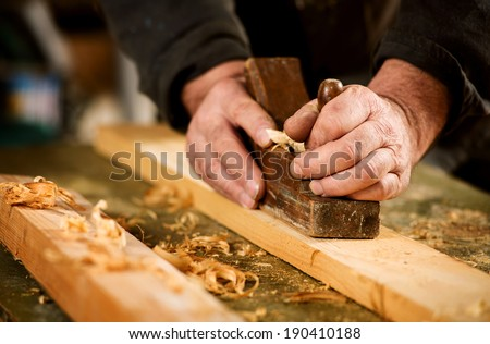Skilled carpenter using a handheld plane to smooth and level the surface of a plank of hardwood, close up view of his hands, the tool and wood shavings - stock photo