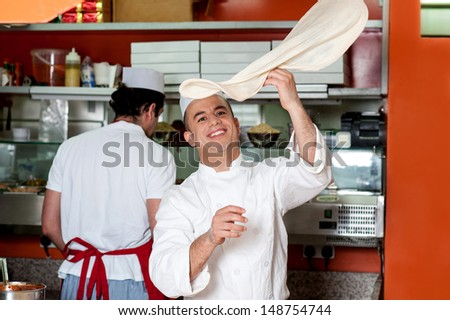Skilled chef throwing up pizza base dough - stock photo