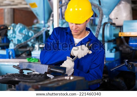 skilled factory mechanic using spanner fasten gumboot making machine - stock photo