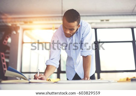Skilled male afro american engineer thinking stock photo download skilled male afro american engineer thinking over blueprint improvement noting ideas in copy book to correct malvernweather Gallery