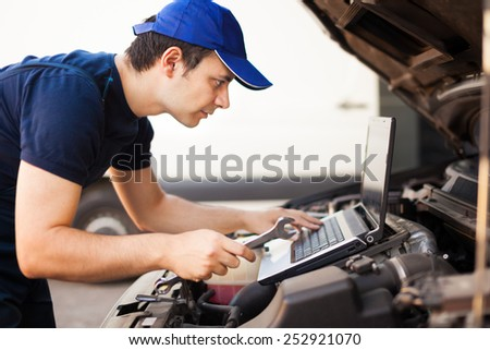 Skilled mechanic using a laptop computer to check a car engine - stock photo