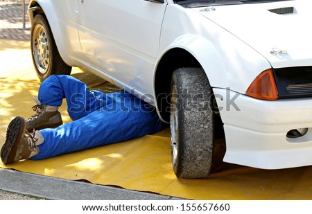 skilled mechanic with the suit from work while repairing the engine failure of the car - stock photo