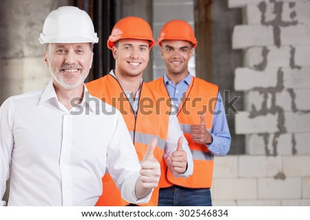 Skilled old architect and young workers are giving thumbs up. Their project was approved. The men are smiling and looking at the camera with happiness. Copy space in right side - stock photo