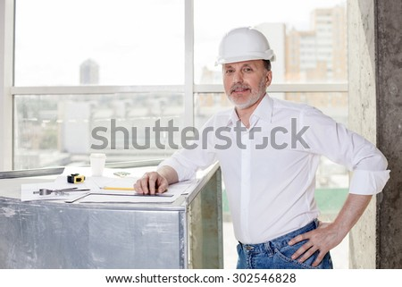 Skilled old architect is drawing sketches of building. He is leaning on a surface where a blueprint is situated. The man is looking forward and smiling - stock photo