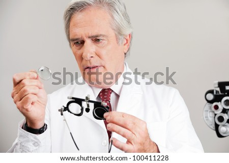 Skilled optometrist examining the lens while holding trial frame for an eye checkup - stock photo