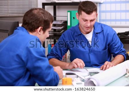 Skilled tradesmen examining a blueprint - stock photo