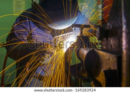 skilled welder during working at workshop - stock photo
