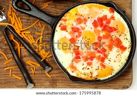 Skillet Baked Eggs with Tomato and Pepper on Table - stock photo