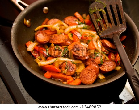 Skillet of sausage and red bell peppers on the stove - stock photo