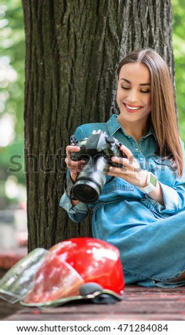 Skillful female photographer using camera in nature