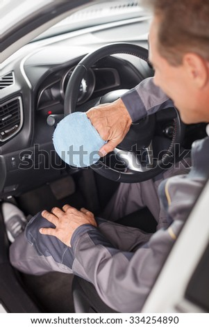 Skillful male auto service worker is cleaning the salon of the car. He is wiping dust from the steering wheel with a cloth. The man is sitting and smiling