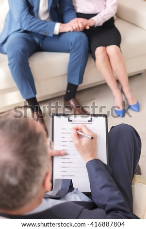 Skillful psychologist is consulting young family - stock photo
