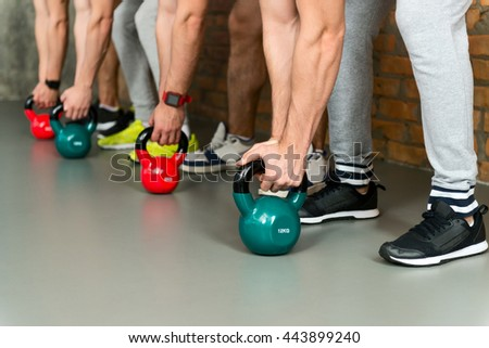 Skillful sportsmen training with weights - stock photo