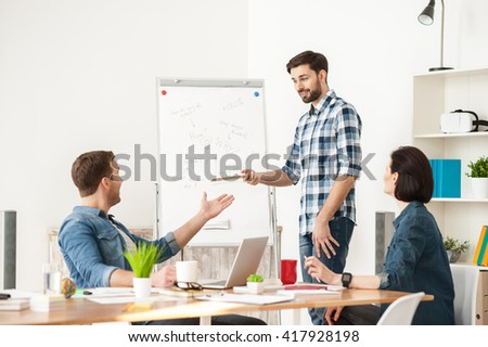 Skillful three colleagues are discussing a project - stock photo
