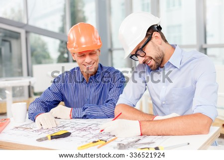 Skillful two architects are discussing the project. They are sitting at the desk and smiling. The young men is drawing a sketch on a blueprint