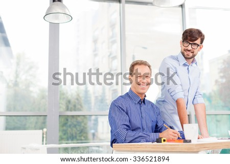 Skillful two architects are working on a new project. They are looking at the camera and smiling. The senior man is sitting and drawing sketch. The young man is standing near him - stock photo