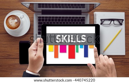 SKILLS, on the tablet pc screen held by businessman hands - online, top view - stock photo